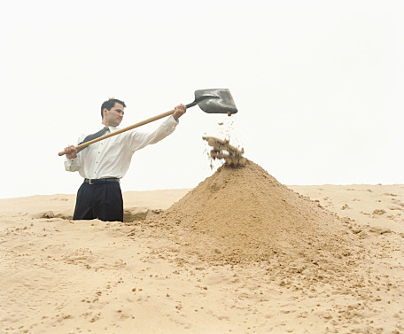 Businessman digging hole in sand dune